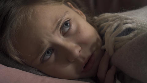 Close-up face of sick caucasian girl coughing while lying under blanket at home Live Action