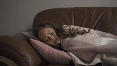 Sick young caucasian girl coughing while lying under blanket at home. The child Live Action