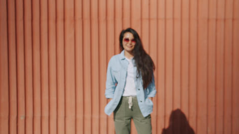 Zoom-in portrait of young Asial lady in sunglasses standing outdoors near wall Footage