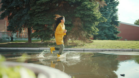 Beautiful Asian woman running in puddles wearing wet clothing raincoat gumboots Footage