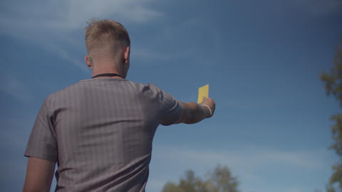 Soccer referee indicating yellow card to player Live Action