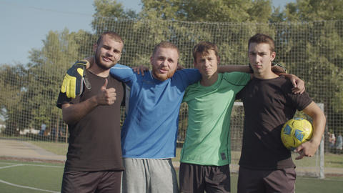 Positive united football team posing on the pitch Footage