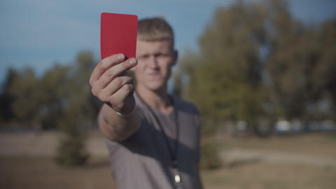 Football referee showing red card on the pitch Footage