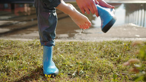 Close-up of hand taking off rubber boot from bare foot and pouring out water Live影片