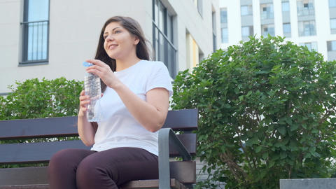 A young woman sits on a bench in an urban setting and drinks water Footage