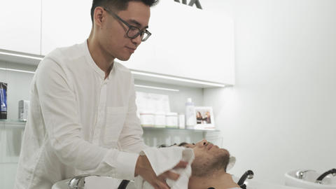 Asian man's hairdresser washes the client's head Footage