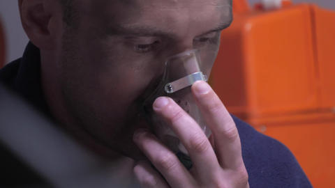 Man in a blanket breath through oxygen mask Live Action