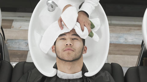 Camera top view Asian man's hairdresser washes the client's head Live Action