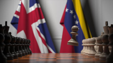 Flags of Great Britain and Venezuela behind pawns on the chessboard. Chess game Live Action