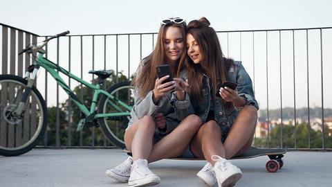 Charming joyful sexy 30s girlfriends sitting on the skateboard and having fun Footage