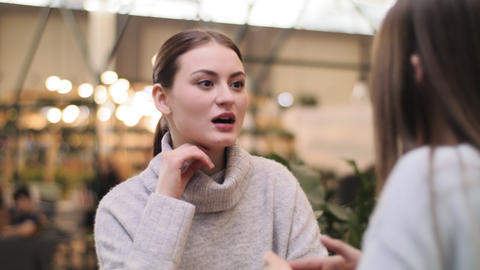 ladies have fun talking at table in cafe at food court Footage