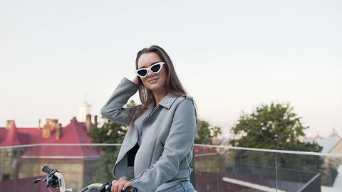 Good-looking smiling young lady in trendy clothes sitting on the bicycle and Footage