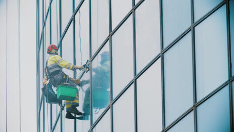 A man worker hanging on ropes and wipes the exterior windows of a business Live Action