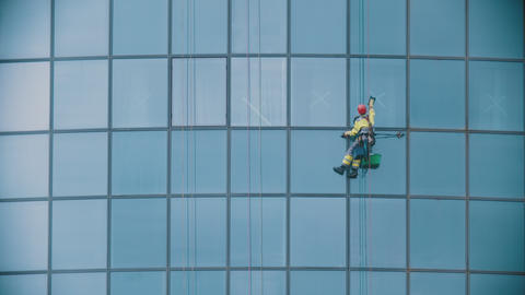 A man worker hanging on ropes by the exterior windows of a business skyscraper Live Action