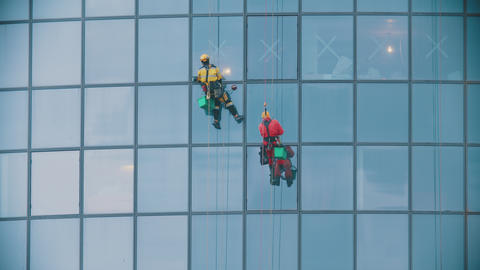 Two men workers in red and yellow work clothes cleaning the exterior windows of Live Action