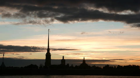Black bell tower spire against tender sunset light, dark clouds quickly run over Footage