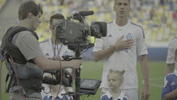 Cameraman with a camera on Steadicam shoots football team sings the national ant Footage