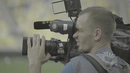 The guy cameraman with a camera on a tripod while shooting at the stadium during Footage