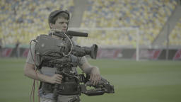 Cameraman with a camera on the Steadicam at the stadium Footage