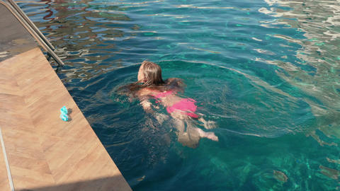 Teenager girl swimming in outdoor water pool in resort hotel. Young girl Live Action