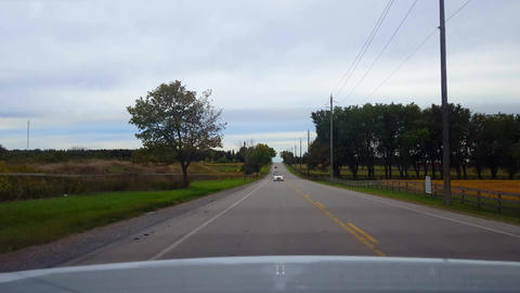Rear View From Back of Car Driving Rural Countryside Road With Rear Traffic Under Overcast Day. Car Live Action