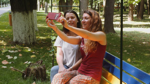 Happy girls taking selfie with the smartphone on a bench in the park Footage
