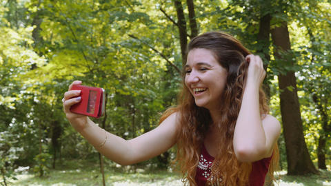 Happy young woman taking selfie with the smartphone in the park Footage
