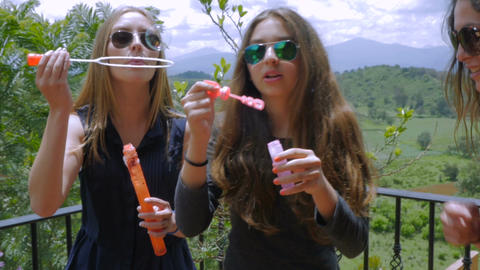 Three beautiful teen girls wearing sunglasses blowing bubbles on a carefree summ Footage