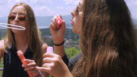 Closeup of two teens having fun outside on a deck in summer with bubbles in slow Footage