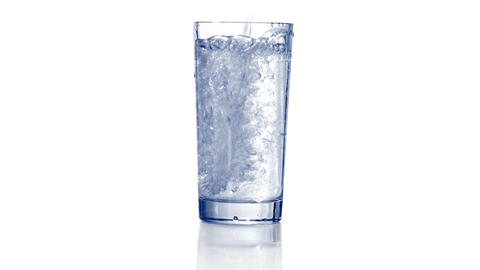Pouring water in empty glass and adding some ice Footage