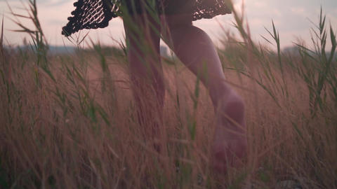 A girl in a dress walks on rocky ground between dry branches of grass. Bare feet Live Action