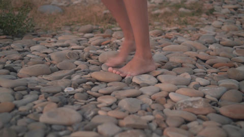 Female tanned legs barefoot walk on the rocky seashore, the girl is uncertain Live Action