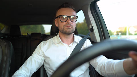 Bearded man in glasses and white shirt driving a car in sunny weather Live Action