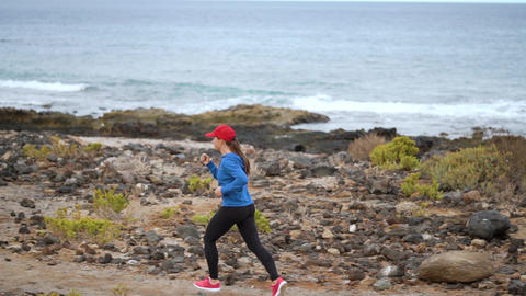 Woman runs along the stony shore of the ocean. Healthy active lifestyle. Slow Footage