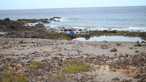 Woman runs along the stony shore of the ocean. Healthy active lifestyle Live Action