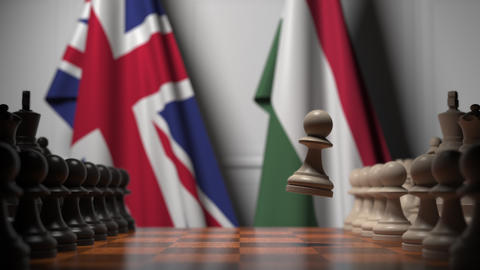 Flags of Great Britain and Hungary behind pawns on the chessboard. Chess game or Live Action