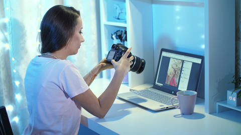 Woman with camera in front of laptop Live Action