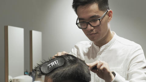 Close-up of an Asian hairdresser with glasses shaving a client Live Action