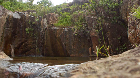 Water Flows out of Round Pool with Small Streams from Rock Tops Footage