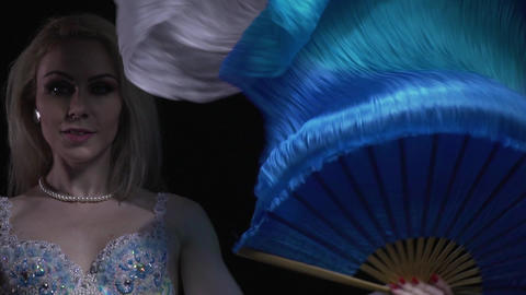 Close up of a young woman with a fan in hand, swinging it in the air, colorful Live Action
