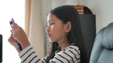Little Asian girl using smartphone select focus shallow depth of field GIF