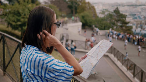 Young woman in Paris checks destinations on the map Footage