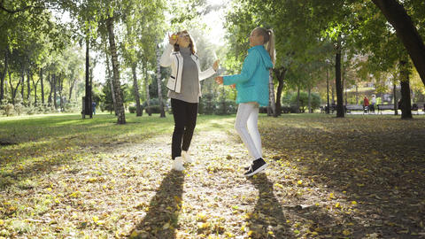 Smiling caucasian women playing soap bubbles in the sunny autumn park. Cheerful Footage