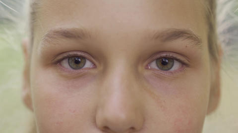 Extreme close-up of a young blond girl with hazel gray eyes looking at the Live Action