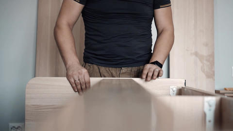 man builds furniture at home GIF