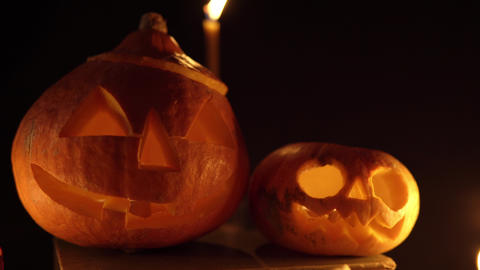 Three pumpkins with terrible grimaces in candlelight on a dark background Live Action