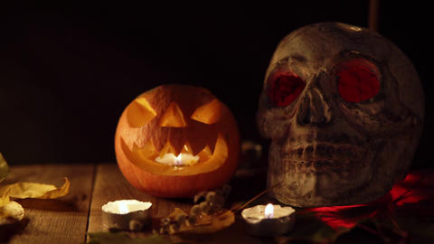 Small toothy pumpkin Jack and a human skull with glowing eyes in candlelight on Live Action