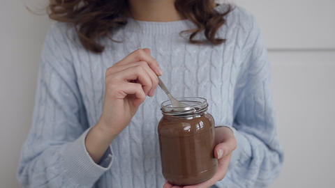 Attractive curly-haired smiling lady enjoying tasty chocolate nutella with Footage