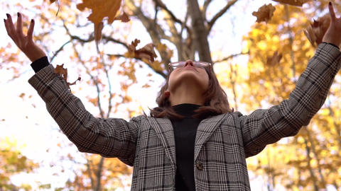 A young woman in glasses throws up yellow leaves up in the autumn forest. Slow Live Action