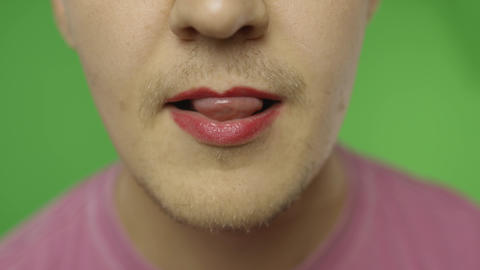 Bearded man with painted lips licks them sexually. LGBT community. Transsexual Live Action